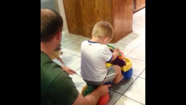 男の子がおもちゃの車に乗って遊ぶのを手伝うワンコがかわいい!