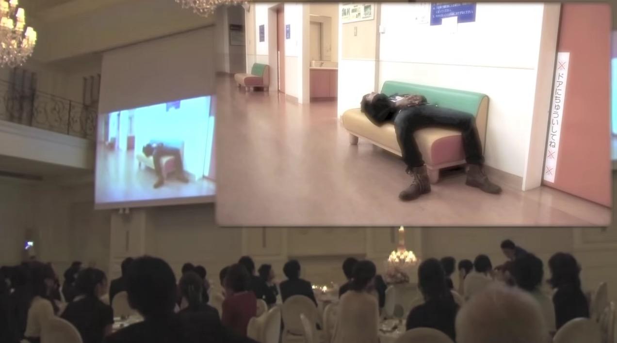 結婚披露宴で、突然イスに寝そべる新郎がスクリーンに映り、、、