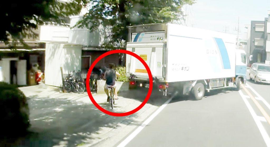 どっちもどっち?無謀な自転車がバックするトラックの隙間を無理に通ってあわや大惨事