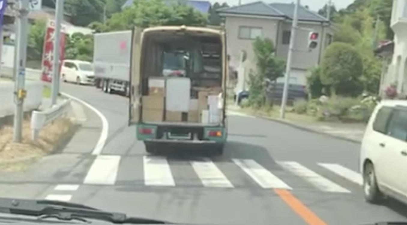 荷台の扉が開いたままの宅配便、荷物を落として気付かず行ってしまう