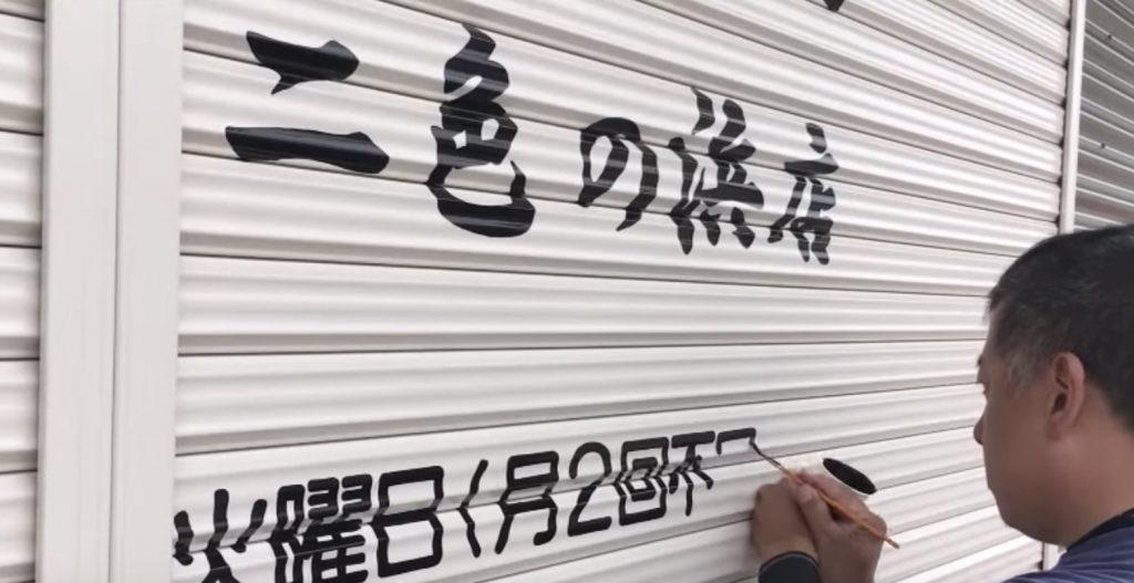 【職人技】でこぼこのシャッターに、下書きなしで綺麗な文字を書く看板職人がスゴい!