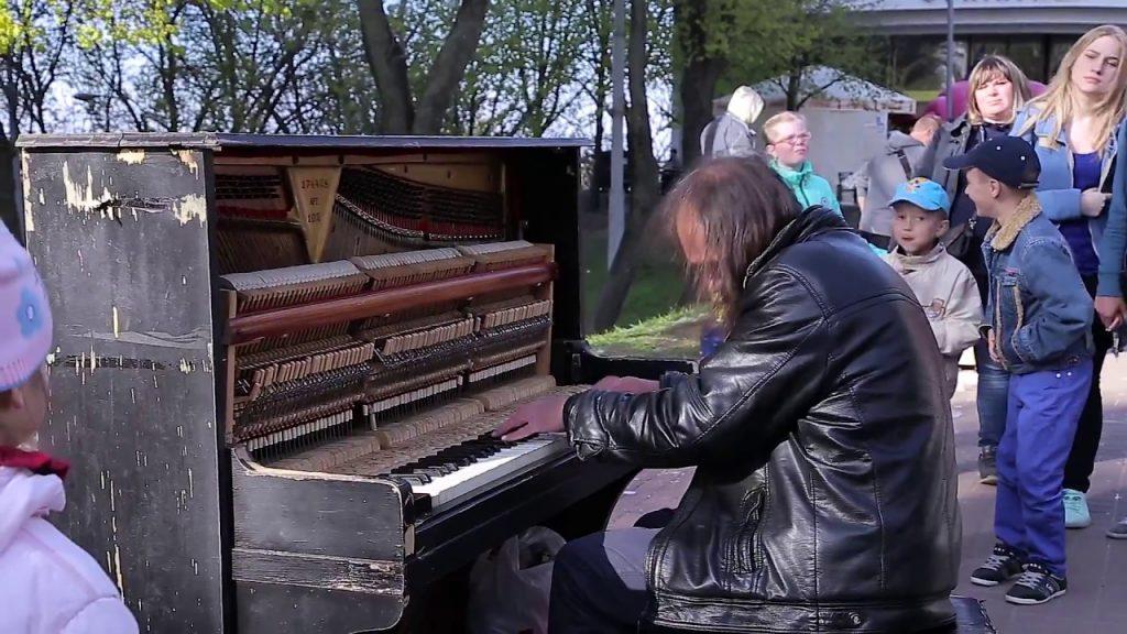 路上でボロボロのピアノで演奏する浮浪者風の男性。しかし、その美しい旋律は人々の心の琴線に触れた