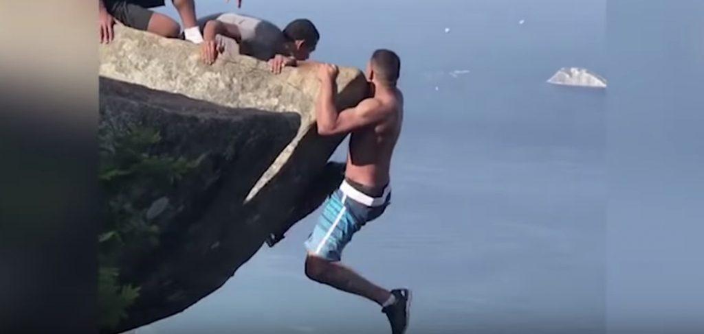 高所の岩にぶら下がって写真を撮ろうとした男性。しかし自力で戻れなくりヤバすぎる状況に