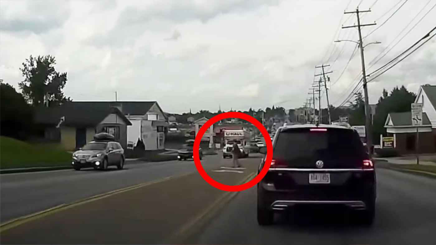 横断歩道ではない場所を渡り、車に中指を立てて前方を見ないで歩いていた女性、自業自得なことになってしまう!