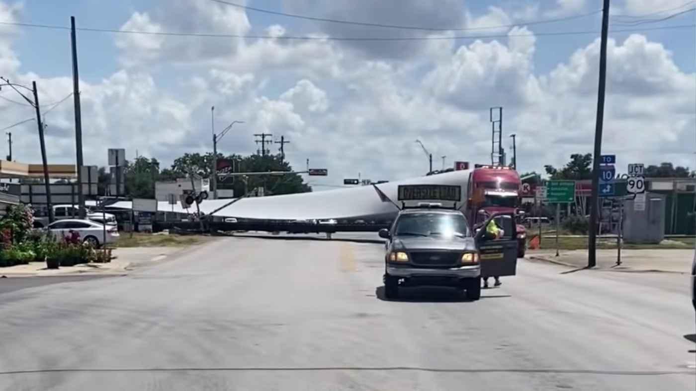 風力発電の巨大な羽根を輸送中のトレーラートラック。しかし踏切を渡り切る前に列車が来てしまう!